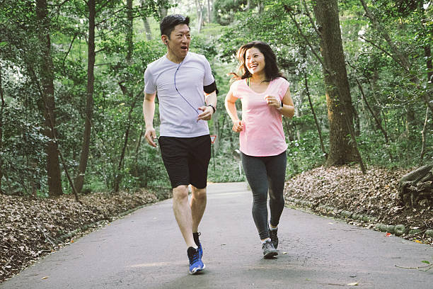 Cheerful Japanese couple running outdoors in a park圖像檔
