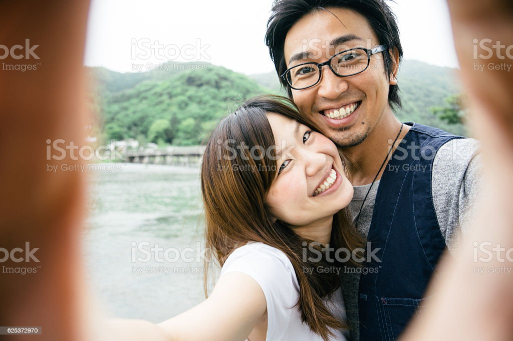 Cheerful Japanese couple taking selfie outdoors in a park圖像檔