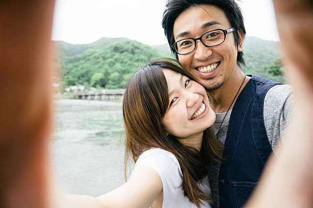 Cheerful Japanese couple taking selfie outdoors in a park stock photo