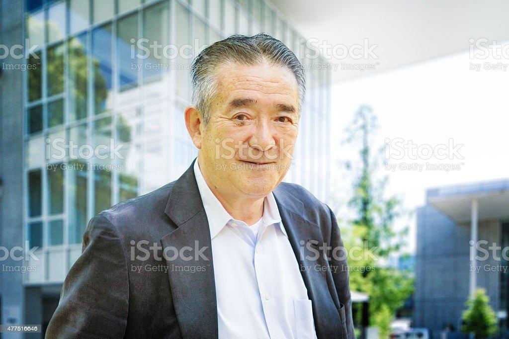 Cheerful Japanese senior man in modern Tokyo urban setting stock photo