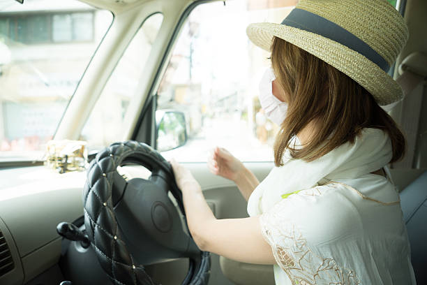 Cheerful Japanese woman driving car wearing anti-pollution mask Cheerful Japanese woman driving car, she is wearing an anti-pollution mask, cityscape on background. antipollution stock pictures, royalty-free photos & images