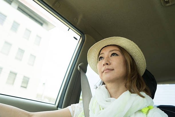 Cheerful Japanese woman driving car wearing - foto de stock