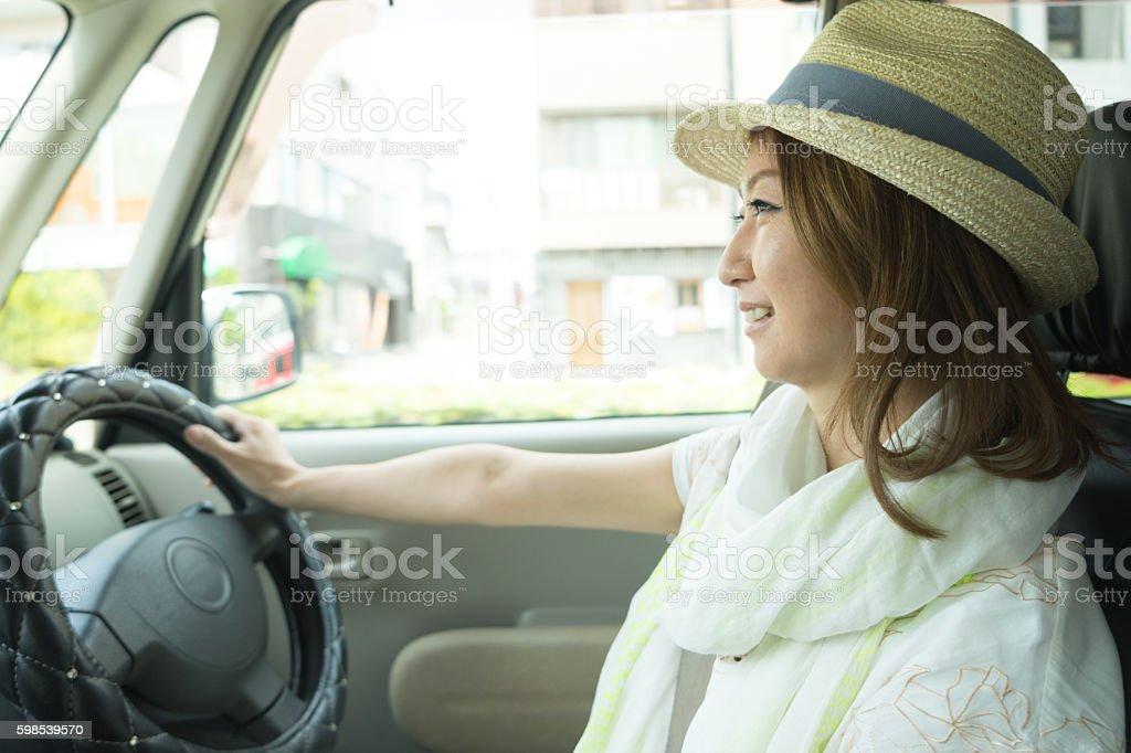 Cheerful Japanese woman driving car wearing photo libre de droits