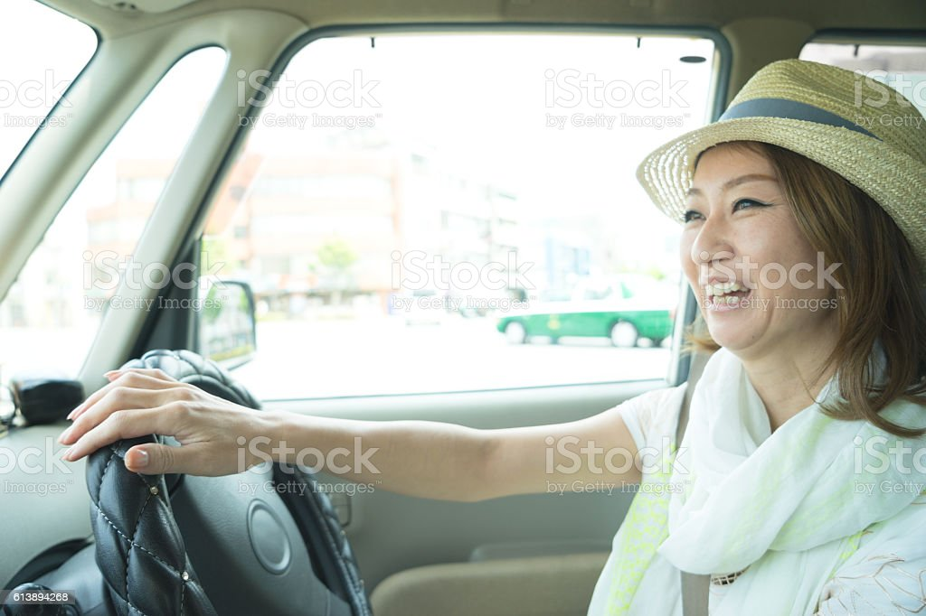 Cheerful Japanese woman driving car wearing - foto de stock