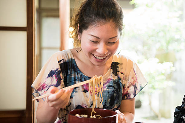 Cheerful Japanese woman eating noodles with chopsticks, smiling stock photo