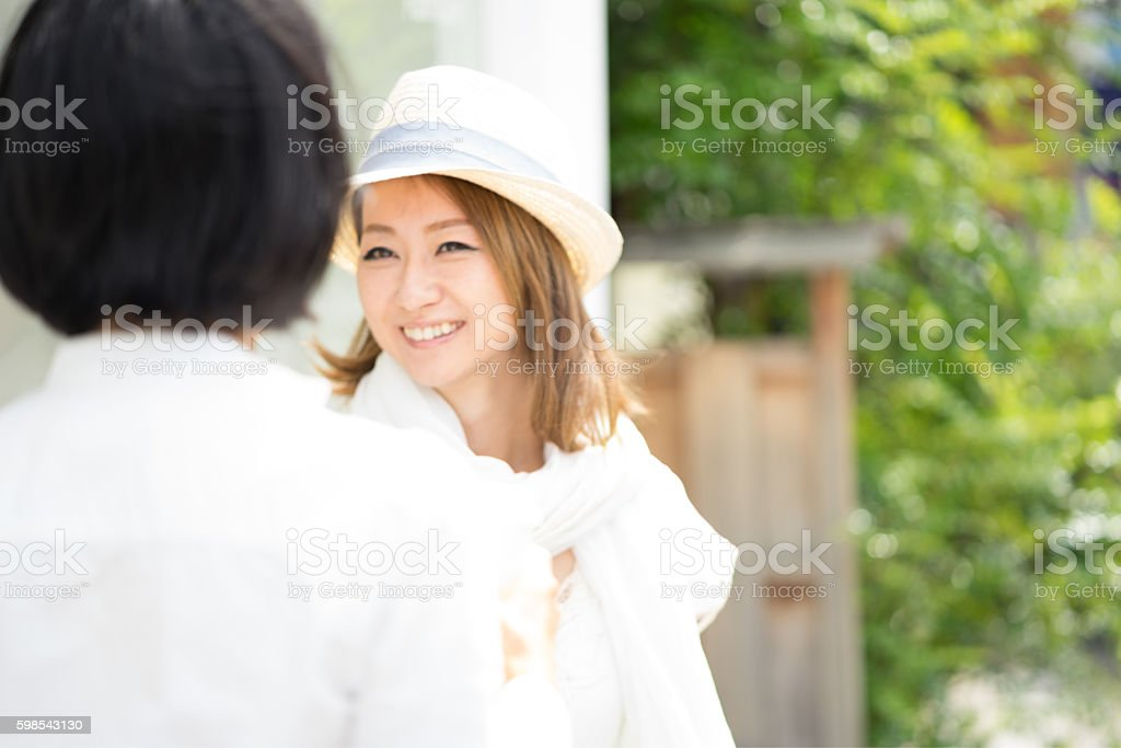 Cheerful Japanese women having a walking meeting, cityscape on background photo libre de droits