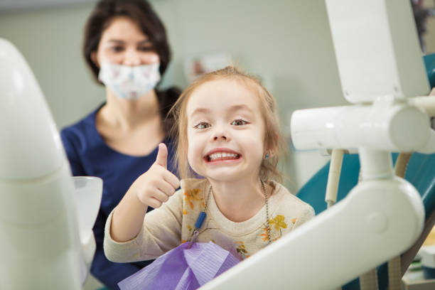 Cheerful kid with broad smile after teeth polishing procedure Cheerful kid with broad smile after painless teeth polishing procedure sits in comfortable chair at modern dentist office with mother and doctor in ask who stand behind. dental health stock pictures, royalty-free photos & images