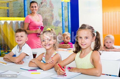 joyful smiling little school children doing lessons at school desks
