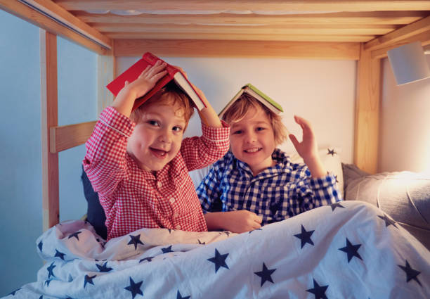 cheerful kids, brothers having fun, playing with books on the bunk bed during bedtime stock photo