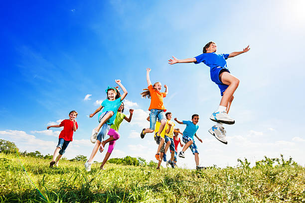 cheerful kids jumping in field against the sky. - african youth jumping for joy stock photos and pictures