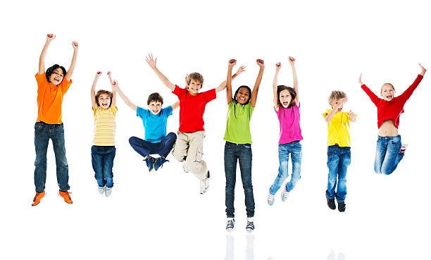 cheerful kids jumping with arms up. - african youth jumping for joy stock photos and pictures