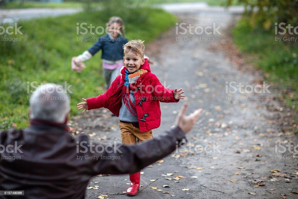 Cheerful kids running towards their grandparent in nature. stock photo
