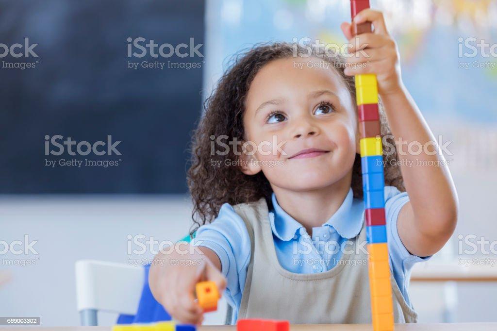 Cheerful kindergarten student plays with blocks stock photo