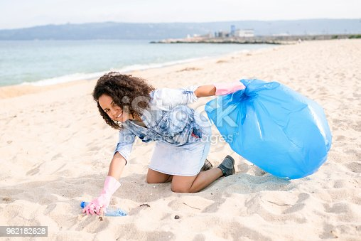 962184460 istock photo Cheerful lady during local clean up at the beach 962182628