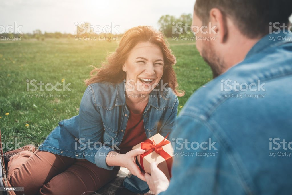 Cheerful lady receiving present box from husband in the nature - Royalty-free Adult Stock Photo