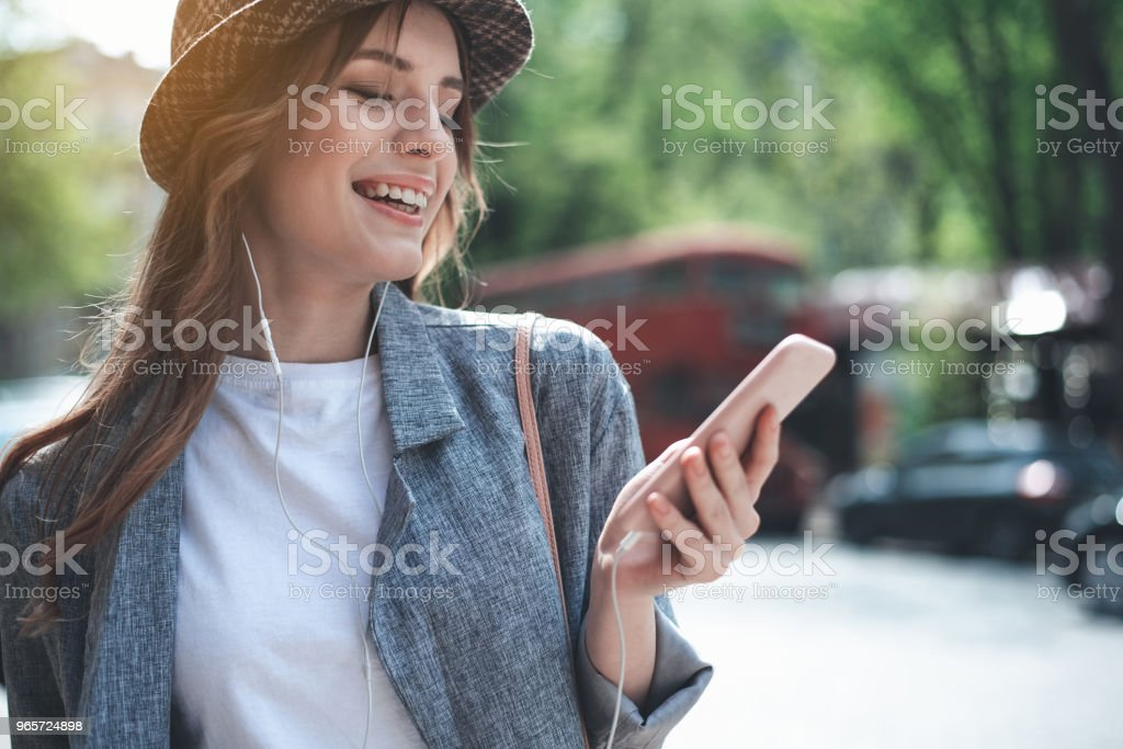 Cheerful lady using mobile phone and headphones - Royalty-free Adult Stock Photo