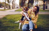 Happy young female smiling for camera and hugging cute Beagle while kneeling on green lawn on city street