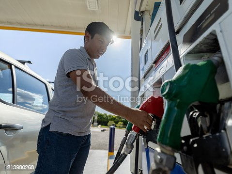 Cheerful latin american customer at a self service gas station refueling his car - Business concepts
