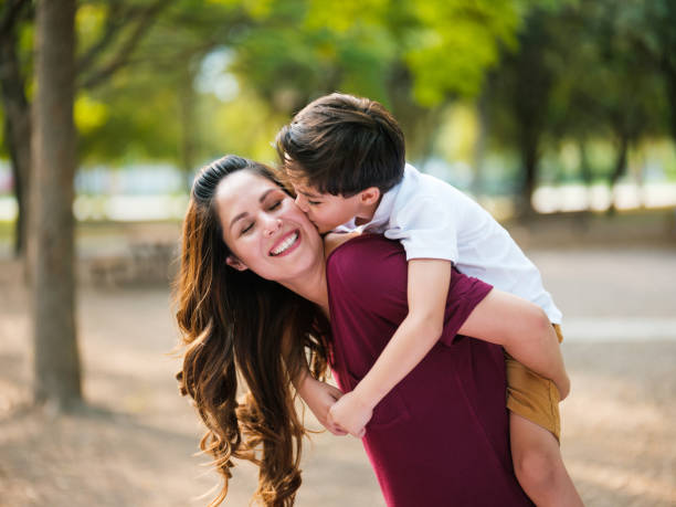Cheerful latin mother carrying son on back and smiling stock photo