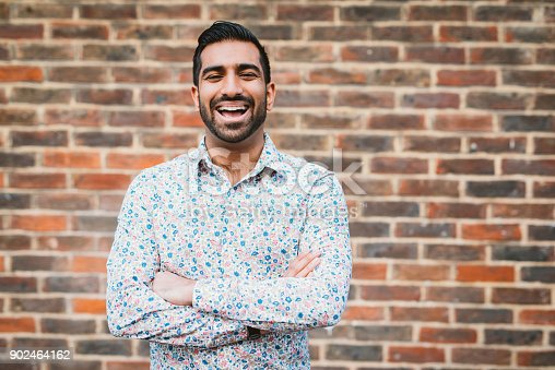 istock Cheerful laughing Indian man in casual shirt near the brick wall 902464162