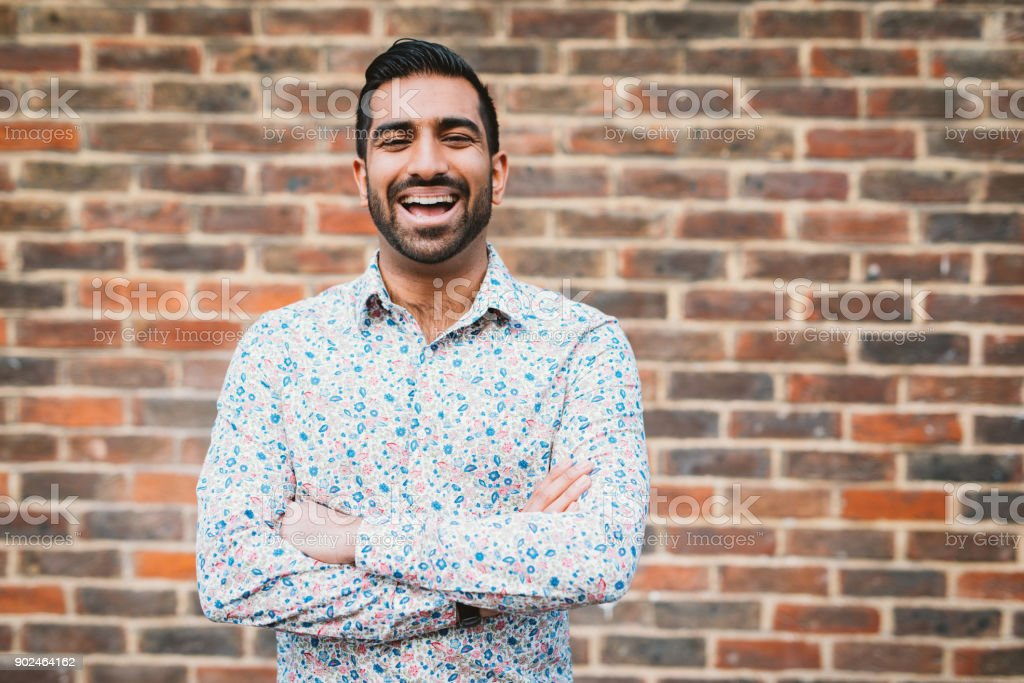 Cheerful laughing Indian man in casual shirt near the brick wall stock photo