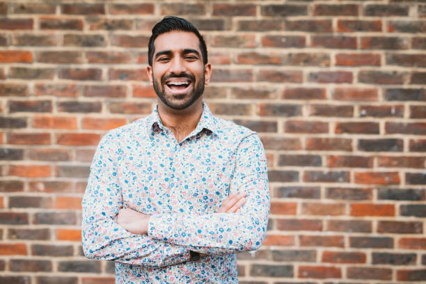cheerful laughing indian man in casual shirt near the brick wall - indian man stock photos and pictures