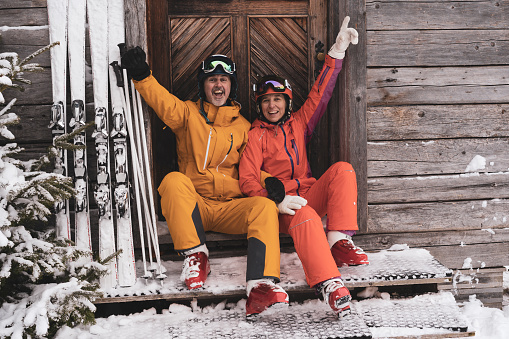 cheerful very happy mature adult sporty ski couple sitting at wooden mountain hut smiling laughing at camera