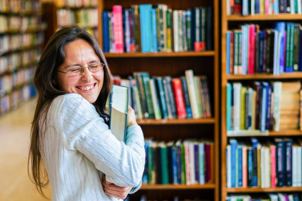 Cheerful Librarian. Are books part of your life? Be a Librarian. Cheerful female librarian enjoying her work day, ranging the books on the shelves. Finding interesting moments, while working in a peaceful atmosphere. illiteracy stock pictures, royalty-free photos & images