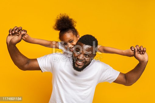 Happy family game. Cheerful little african american girl riding on daddy's back, orange background
