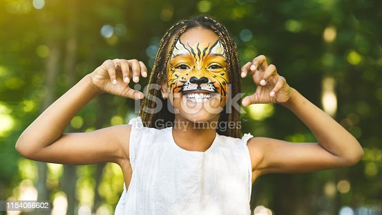 Scary tiger cub. Cheerful little african-american girl with face painting like tiger roaring and showing claws on camera, laughing and playing in park