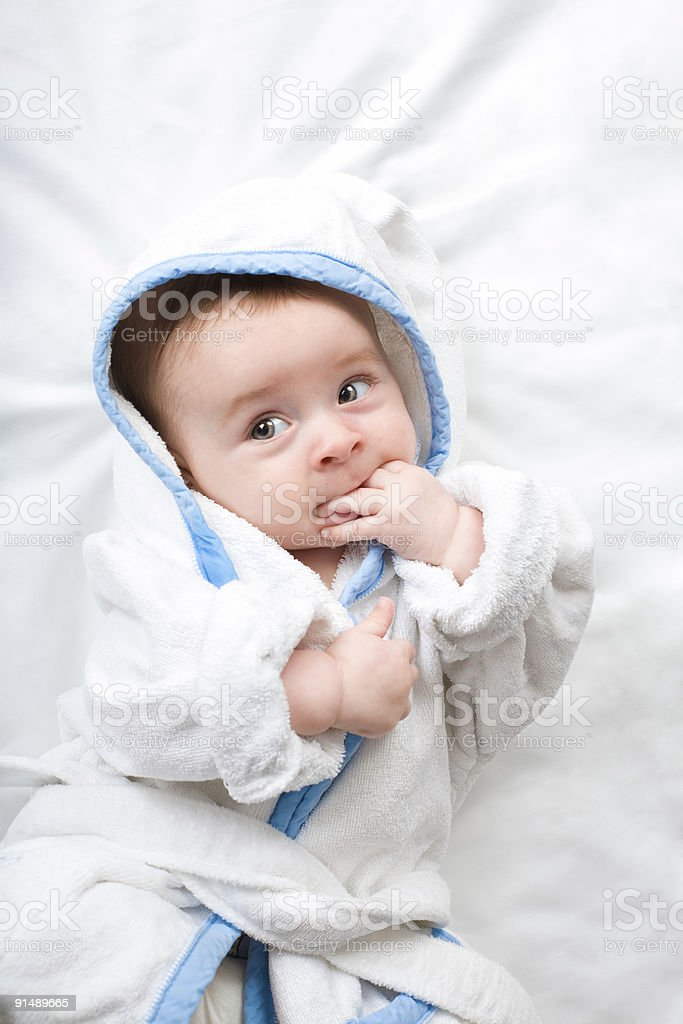 cheerful little baby with white robe  and hand in mouth royalty-free stock photo