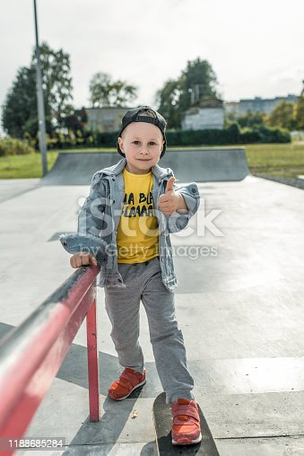 Cheerful little boy 3-5 years old, hand gesture finger to top like, great and super. Training and learning to ride skateboard. Autumn day in summer in city. Casual wear, denim pants, baseball cap