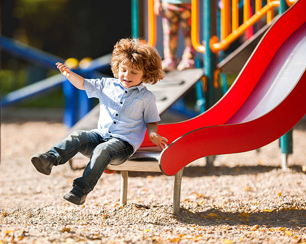 cheerful little boy having fun while sliding outdoors. - sliding stock photos and pictures