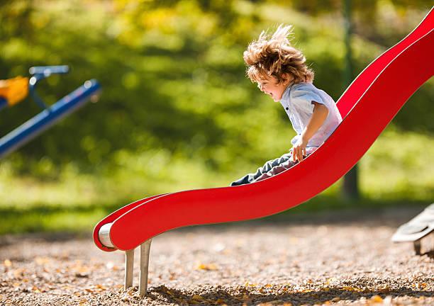 Cheerful little boy having fun while sliding outdoors. stock photo
