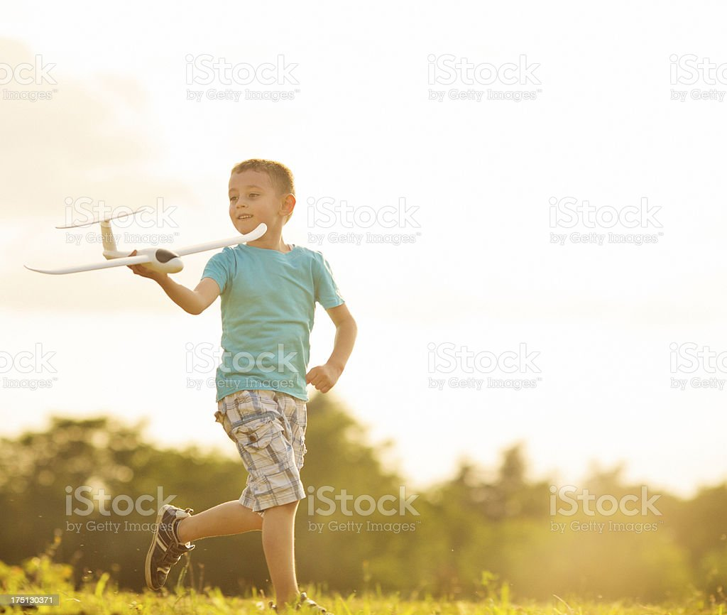 Cheerful Little Boy Having Fun With Toy Airplane Outdoors. stock photo