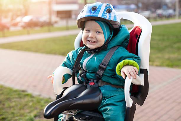 Cheerful little boy in a bike seat stock photo