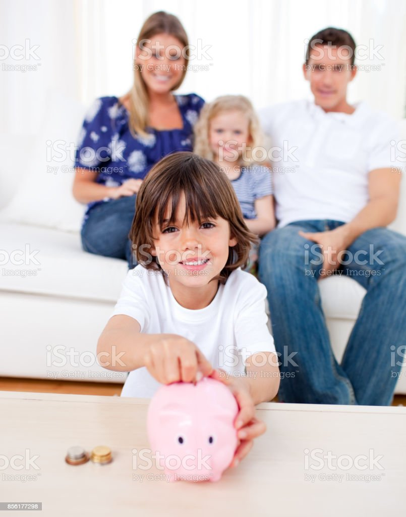 Cheerful little boy inserting coin in a piggybank stock photo