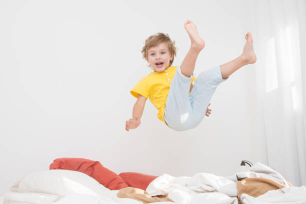 fröhliche kleine junge springen auf bett zu hause - bett für jungs stock-fotos und bilder