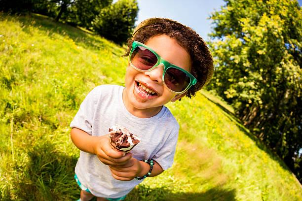 fröhlich kleiner junge lecken eis an einem sonnigen tag - sonnenbrille kleinkind stock-fotos und bilder