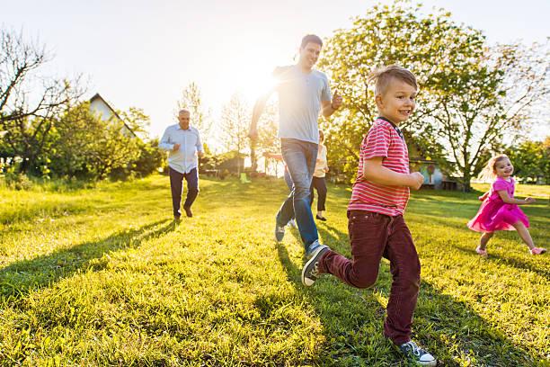 cheerful little boy running in nature with his family. - mãe criança brincar relva efeito de refração de luz imagens e fotografias de stock