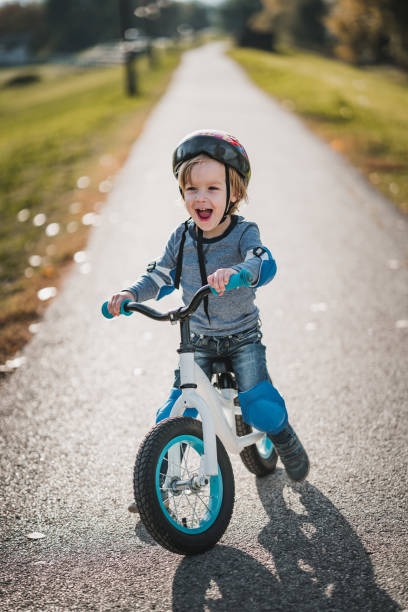 Cheerful little boy shouting while riding bicycle in the park. stock photo