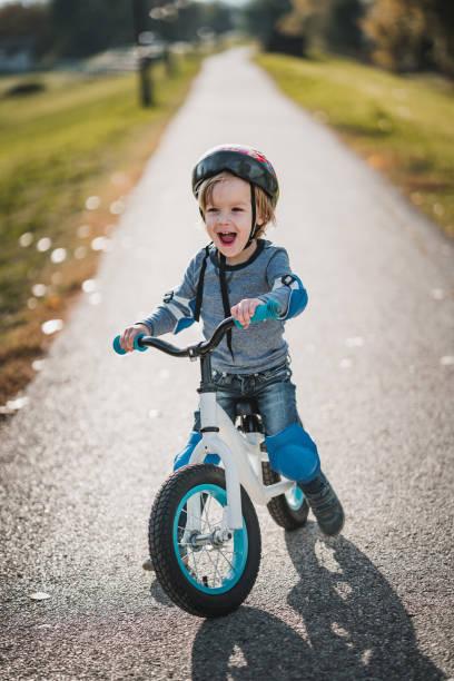 cheerful little boy shouting while riding bicycle in the park. - kask sportowy zdjęcia i obrazy z banku zdjęć