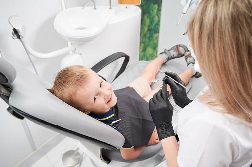 Cheerful little boy sitting in dental chair in dental office.