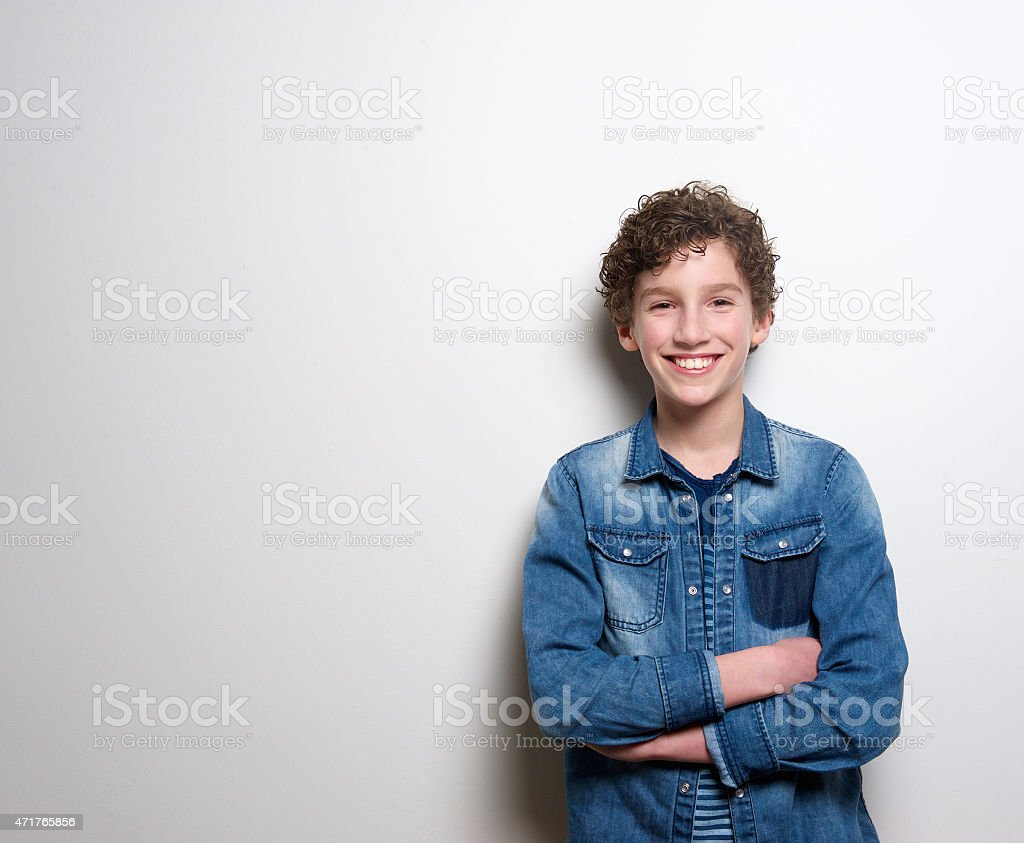 Cheerful little boy smiling with arms crossed stock photo