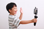 istock Cheerful little boy using smartphone and mini tripod filming video, vlogging 1213805868