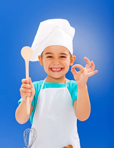 Cheerful little chef showing good taste stock photo