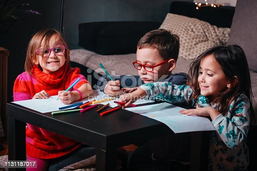 983418152 istock photo Cheerful little children having fun doing finger painting 1131187017