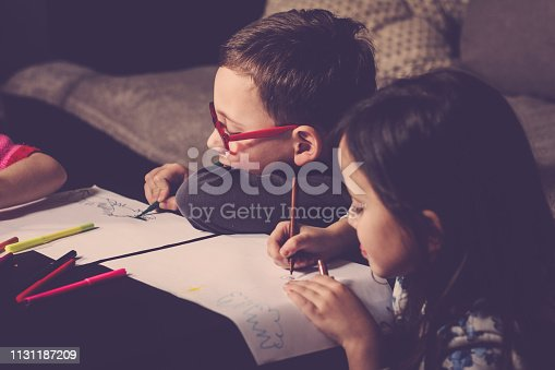 983418152 istock photo Cheerful little children having fun doing finger painting 1131187209