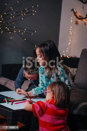 983418152 istock photo Cheerful little children having fun doing finger painting 1131188874