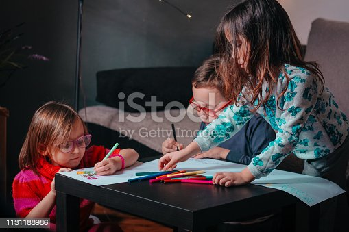 983418152 istock photo Cheerful little children having fun doing finger painting 1131188986